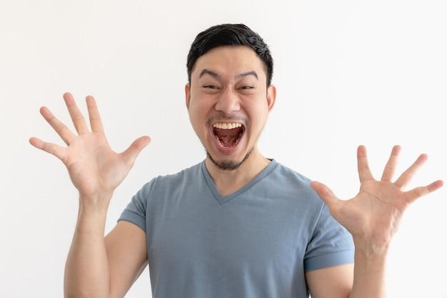 Verrast en wauw gezicht van aziatische man in blauw t-shirt op geïsoleerde ruimte.