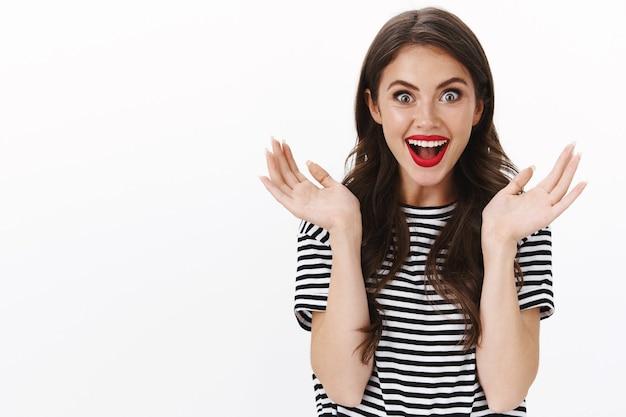 Verrast enthousiaste europese vrouw in gestreept t-shirt, rode lippenstift kijkt verbaasd en geamuseerd, steekt handen omhoog gebarend opgewonden hoor geweldig nieuws, reageer geweldig nieuws, witte muur