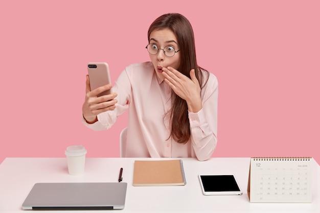 Verrast europese jonge vrouwelijke kantoormedewerker bedekt mond met verbazing, houdt mobiele telefoon in de hand