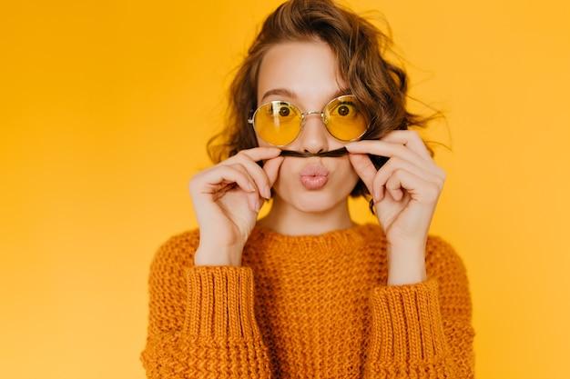 Verrast europese vrouw met bruine ogen spelen met haar korte haar