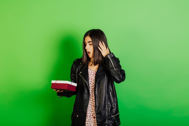 Verrast feestvarken draagt stijlvolle leren jas staande op groene muur met geschenkdoos, mond open houden tijdens het ontvangen van cadeau.