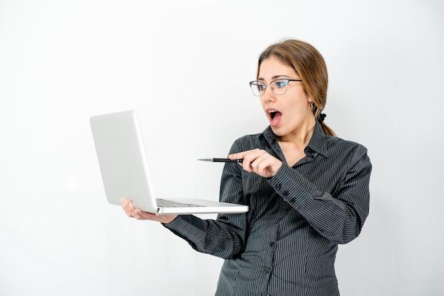 Verrast geïsoleerde mooie jonge vrouw met laptop in de hand wijzend met pen het scherm dragen kantoor zakelijke kleding.