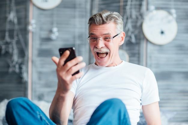 Verrast, gelukkig bebaarde solide man ontspannen op bed en het lezen van nieuws kijken naar de telefoon