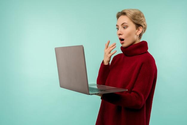 Verrast gelukkig blonde vrouw in trui laptop computerscherm kijken met open mond over blauwe achtergrond