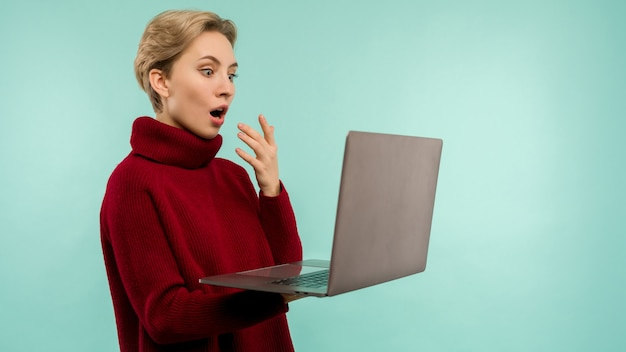 Verrast gelukkig blonde vrouw in trui laptop computerscherm met open mond kijken over blauwe achtergrond - afbeelding