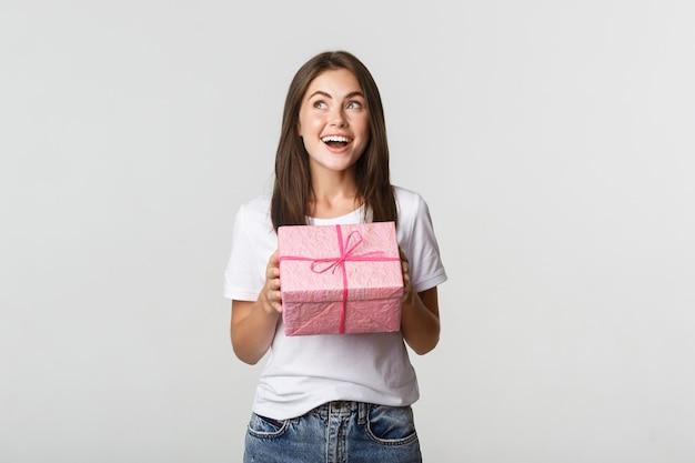 Verrast gelukkig feestvarken dat verpakt wit cadeau ontvangt.