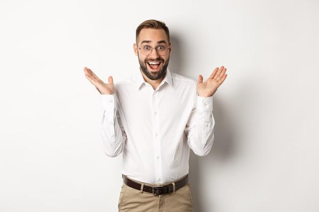 Verrast gelukkig mannelijke ondernemer handen klappen en glimlachen, camera kijken verbaasd, staande op een witte achtergrond.