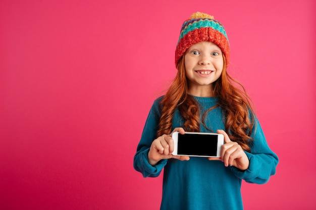 Verrast gelukkig meisje die smartphone met het lege scherm tonen en geïsoleerd glimlachen