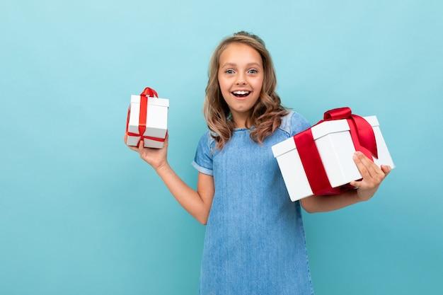 Verrast gelukkig meisje met twee dozen giften op lichtblauw