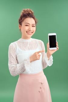 Verrast gelukkige aziatische vrouw die een leeg smartphonescherm toont en erop wijst. geïsoleerde groene achtergrond.