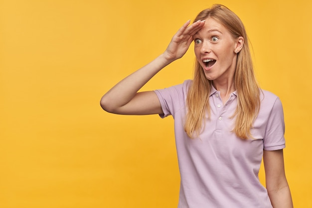 Verrast gelukkige blonde jonge vrouw met sproeten in lavendel t-shirt houdt de hand op de kin en kijkt ver weg over de gele muur