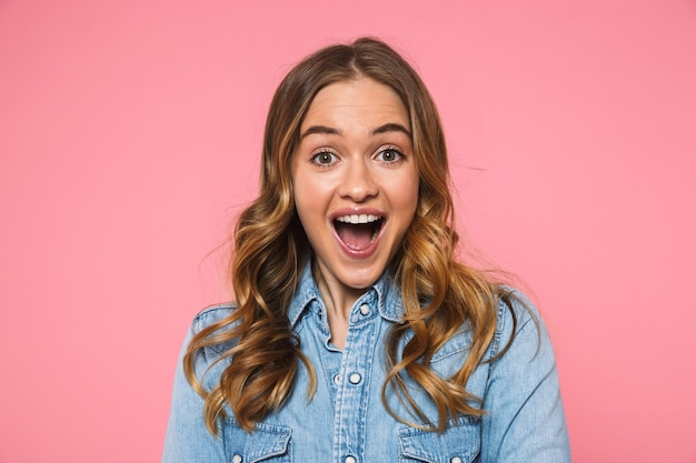 Verrast gelukkige blonde vrouw in denim shirt verheugt zich en kijkt naar de voorkant over roze muur Premium Foto