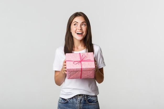 Verrast gelukkige verjaardag meisje verpakt cadeau ontvangen