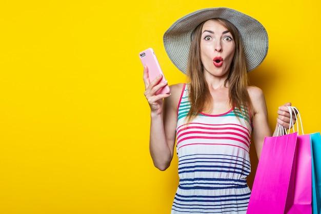 Verrast geschokt jong meisje in hoed met telefoon en boodschappentassen