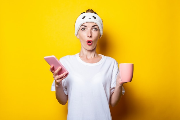 Verrast geschokt jonge vrouw in verband met een telefoon en een kopje koffie op een gele achtergrond
