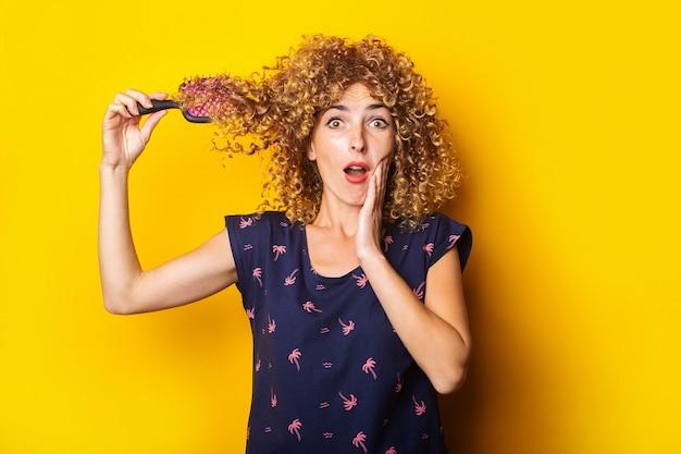 Verrast geschokt jonge vrouw met verwarde kam in krullend haar op gele achtergrond.