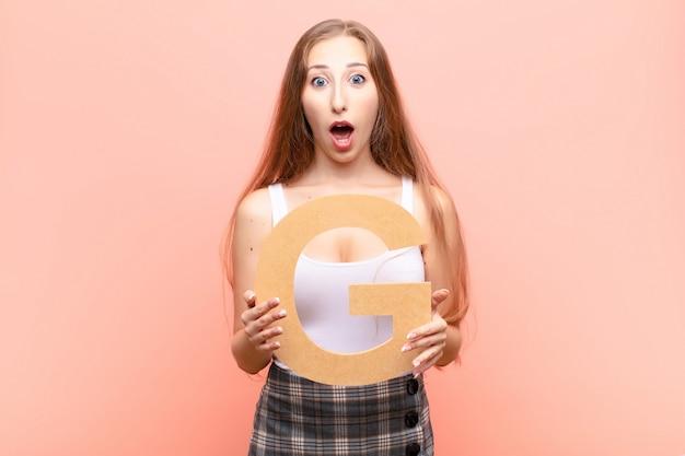 Verrast, geschokt, verbaasd, de letter g van het alfabet vasthoudend om een woord of zin te vormen.
