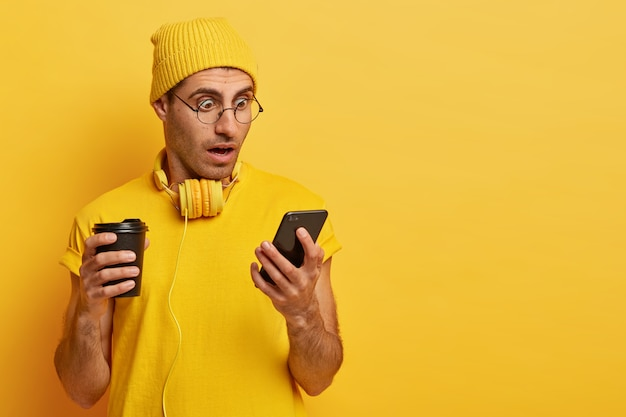 Verrast geschokte man staart naar smartphoneapparaat, draagt doorzichtige bril en gele hoed, drinkt afhaalkoffie, verbaasd over vreselijk nieuws op internet. monochroom, gele kleur