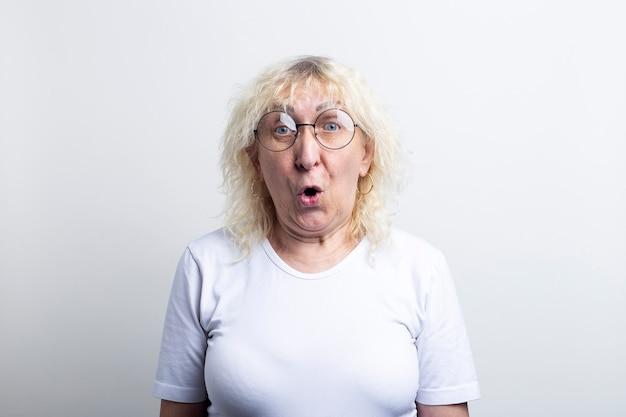 Verrast geschokte oude vrouw met een bril op een lichte achtergrond.
