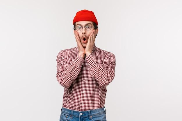 Verrast geschrokken en gefascineerde jonge grappige bebaarde man in rode muts reageert op overweldigend schokkend nieuws, hoort iets aan, staren met ongeloof en verbazing, wangen aanraken