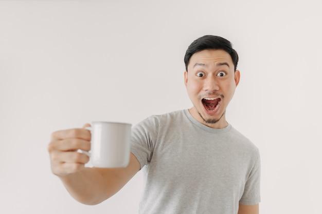 Verrast gezicht van de mens die een kop koffie drinkt die op witte achtergrond wordt geïsoleerd