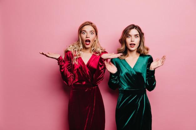 Verrast glamoureuze vrouw in fluwelen jurk staande op roze muur. binnenfoto van verbaasd meisje in groene kledij.