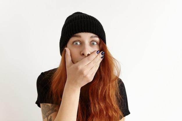 Verrast grappig roodharige meisje met goggle-eyed in stijlvolle zwarte kleding die mond bedekt met hand