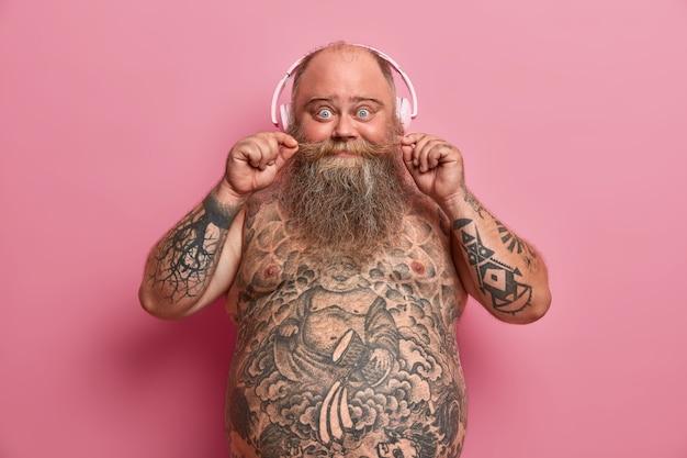 Verrast grappige mollige man houdt snor vast, staat shirtloos over roze muur, heeft dikke buik, tatoeages op buik en armen, koude rillingen met favoriete muziek, draagt een koptelefoon, geniet van nieuwe track
