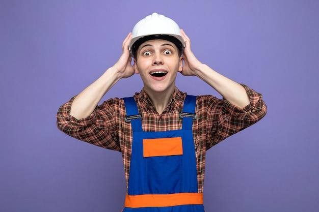 Verrast greep het hoofd van een jonge mannelijke bouwer in uniform