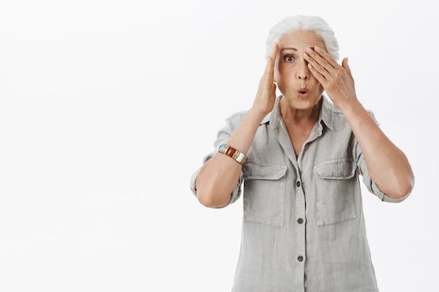Verrast grootmoeder gluren met verbaasde uitdrukking