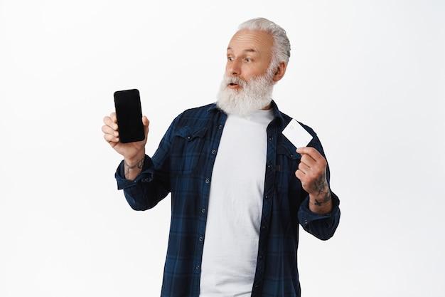 Verrast grootvader die naar het smartphonescherm kijkt terwijl hij een creditcard toont, verbaasd over het online winkelen, staande tegen een witte muur