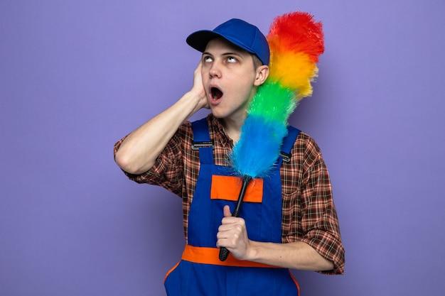 Verrast hand op de wang, jonge schoonmaakster met uniform en pet met pipidastre