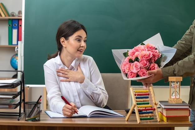 Verrast hand op het hart jonge vrouwelijke leraar schrijft op notitieboekje geeft boeket door iemand die aan tafel zit met schoolhulpmiddelen in de klas