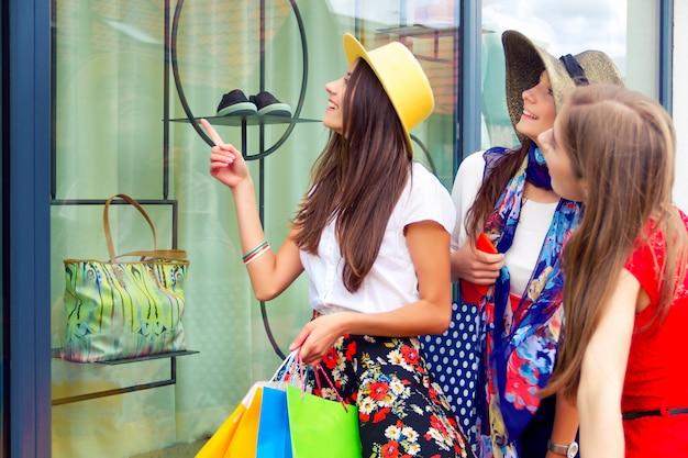 Verrast heldere vrouwen vrouwtjes meisjes vrienden in kleurrijke jurken en hoeden in winkelcentrum op zoek naar nieuwe mode kleding in etalage.