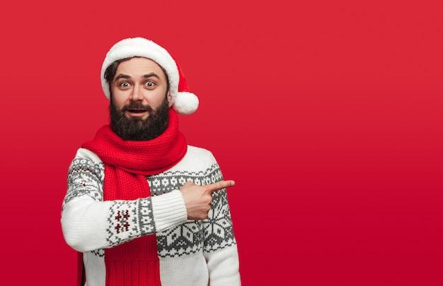 Verrast hipster in kerstmuts opzij wijzend