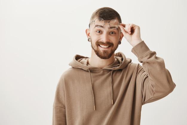 Verrast hipster man met baard, glimlachend gelukkig en opstijgen bril