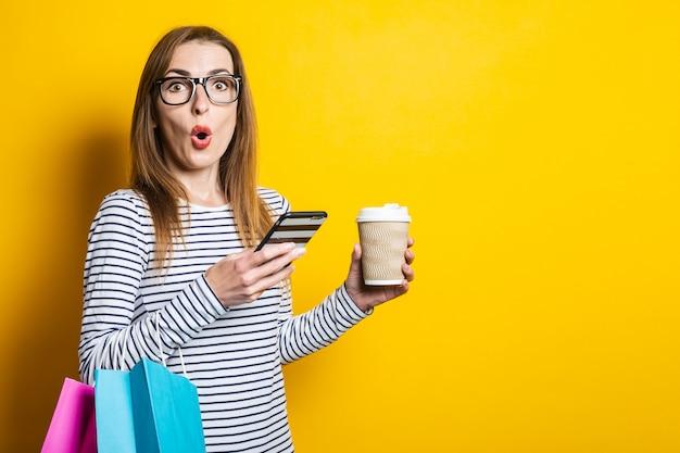 Verrast in shock jong meisje kijkt naar de telefoon, met een papieren beker met koffie en met boodschappentassen op een gele achtergrond