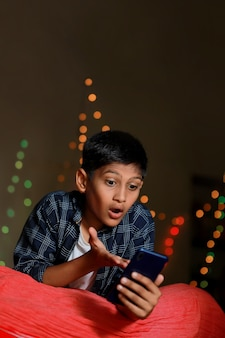Verrast indisch klein kind na het zien in slimme telefoon