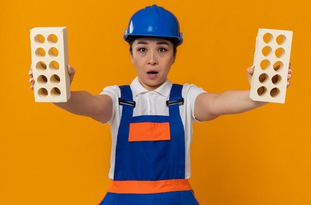 Verrast jong aziatisch bouwersmeisje met blauwe veiligheidshelm die bakstenen houdt