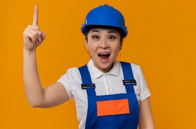 Verrast jong aziatisch bouwersmeisje met blauwe veiligheidshelm die naar boven wijst
