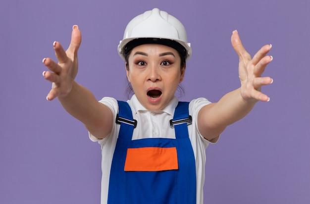 Verrast jong aziatisch bouwersmeisje met witte veiligheidshelm die haar handen uitstrekt