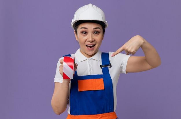 Verrast jong aziatisch bouwmeisje met een witte veiligheidshelm die vasthoudt en wijst op waarschuwingstape