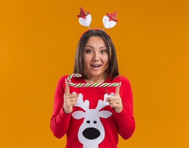 Verrast jong aziatisch meisje dat de hoepel van het kerstmishaar met sweater draagt die kerstmissuikergoed houdt dat op oranje muur wordt geïsoleerd