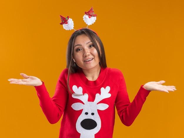 Verrast jong aziatisch meisje dat de hoepel van het kerstmishaar met sweater spreidende handen draagt die op oranje muur worden geïsoleerd