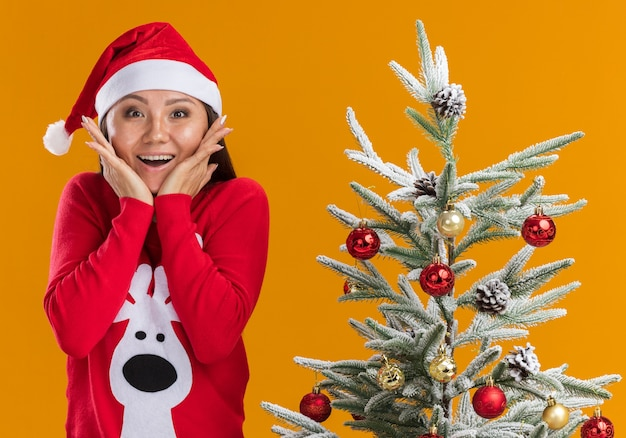 Verrast jong aziatisch meisje met kerstmuts met trui staande in de buurt van kerstboom bedekte mond met handen geïsoleerd op een oranje achtergrond