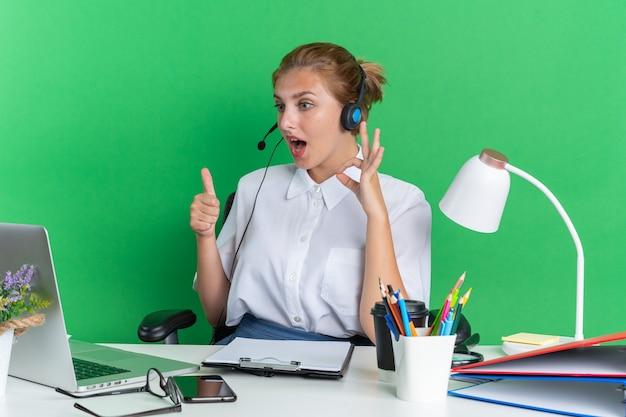 Verrast jong blond callcentermeisje met een hoofdtelefoon die aan een bureau zit met uitrustingsstukken die naar een laptop kijken die duim omhoog doet en een goed teken doet