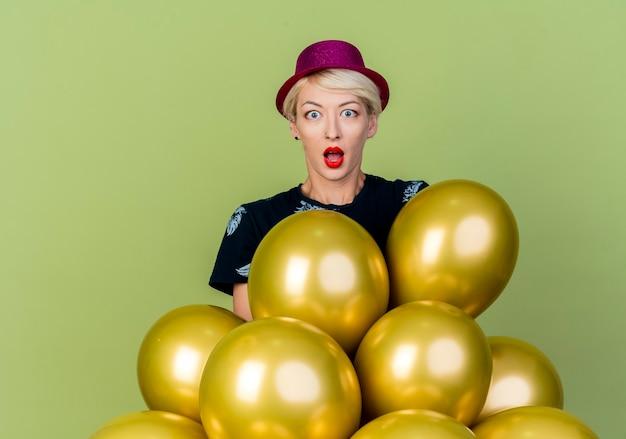 Verrast jong blond feestmeisje met feestmuts achter ballonnen kijken naar camera geïsoleerd op olijfgroene achtergrond