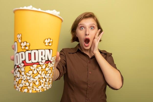 Verrast jong blond meisje dat een emmer popcorn uitrekt en hand op het gezicht zet dat op een olijfgroene muur is geïsoleerd met kopieerruimte