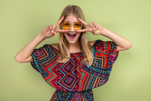 Verrast jong blond slavisch meisje met zonnebril gebaren overwinningsteken
