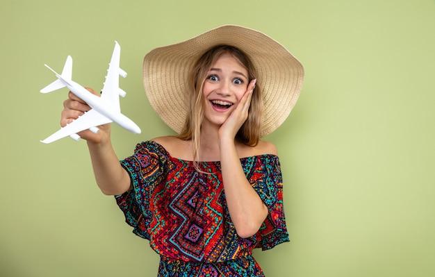 Verrast jong blond slavisch meisje met zonnehoed die hand op haar gezicht legt en vliegtuigmodel vasthoudt